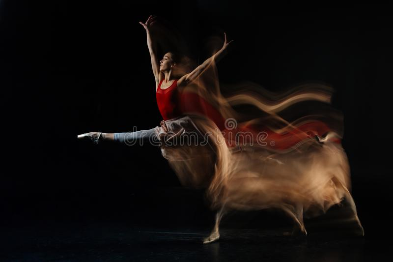 Attractive professional dancer showing a performance. Professional performance. Attractive nice female dancer standing against black background and showing her royalty free stock images