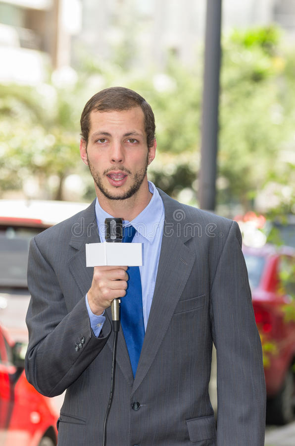 Attractive professional male news reporter wearing stock photography