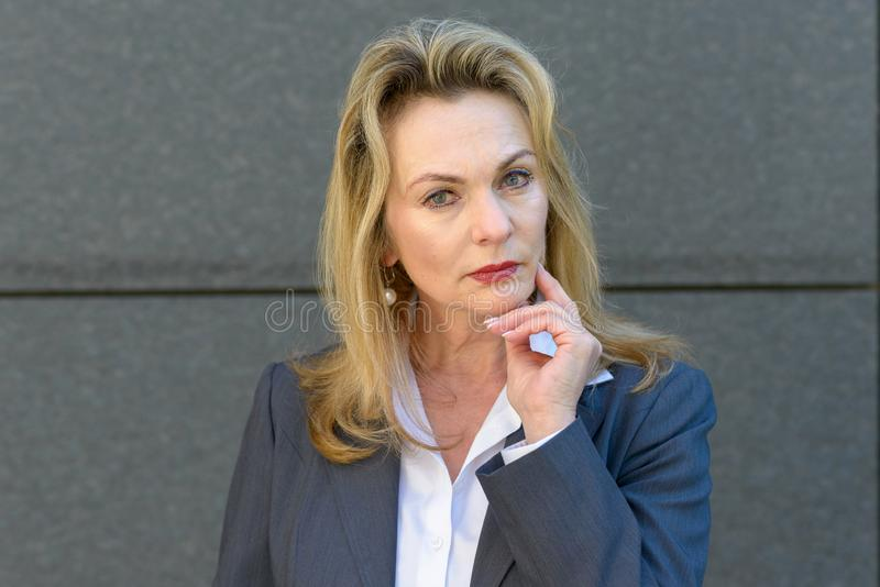 Attractive professional woman deep in thought. Staring intently at the camera with her hand to her chin against a grey exterior stone wall royalty free stock images
