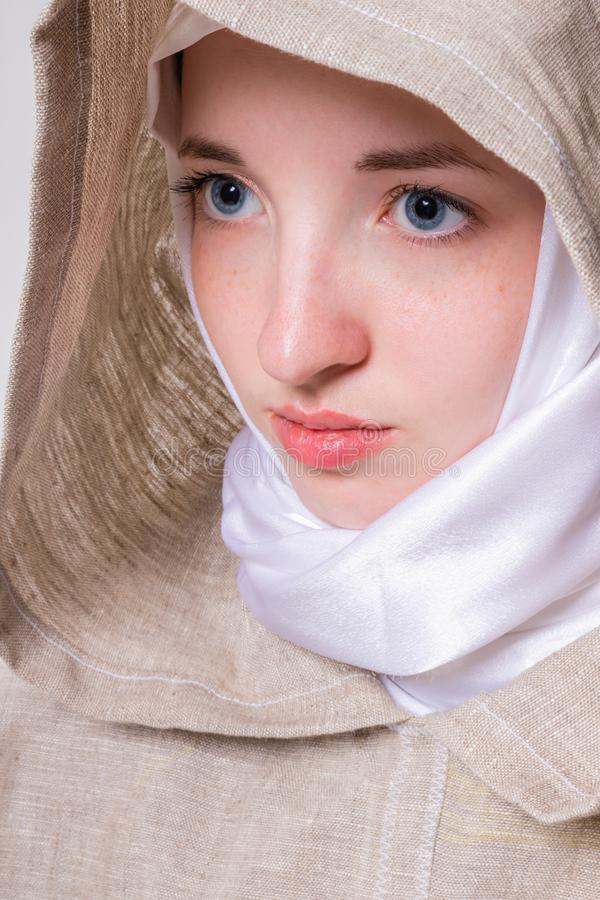 Attractive pure girl with a clear look in a white scarf addresses prayer to God stock photos