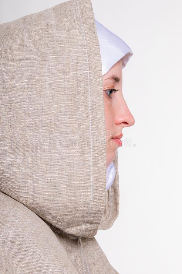 Lovely pure girl in white scarf and monastic clothes stock images