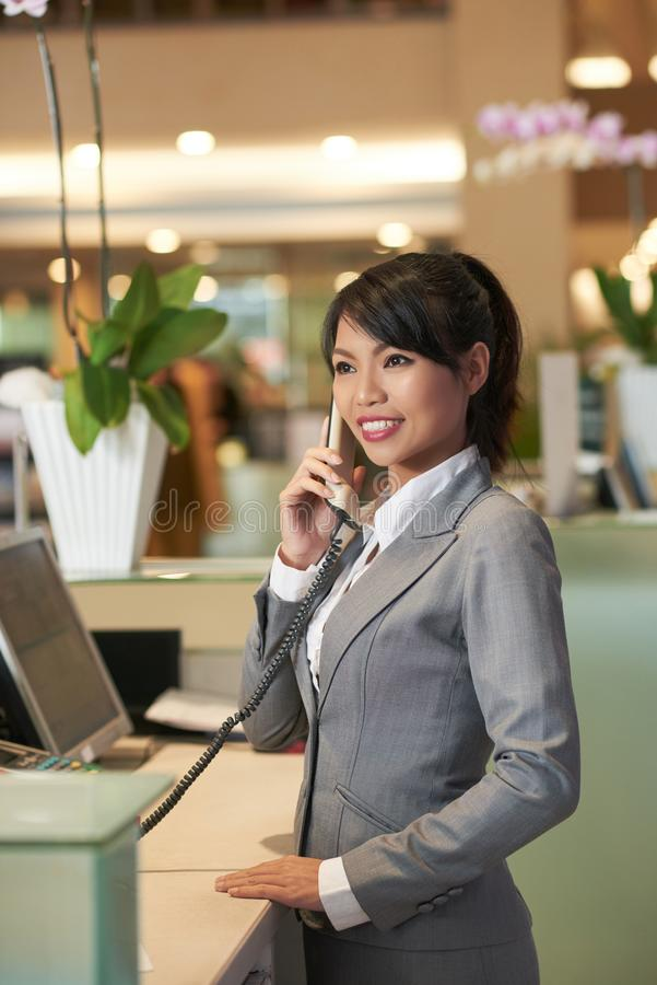 Attractive receptionist. Pretty female receptionist calling on the phone royalty free stock image
