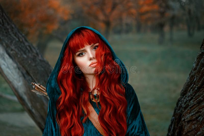Attractive red-haired girl looking at the camera with brown eyes, wearing blue velor velvet cloak with hood on her head stock photography