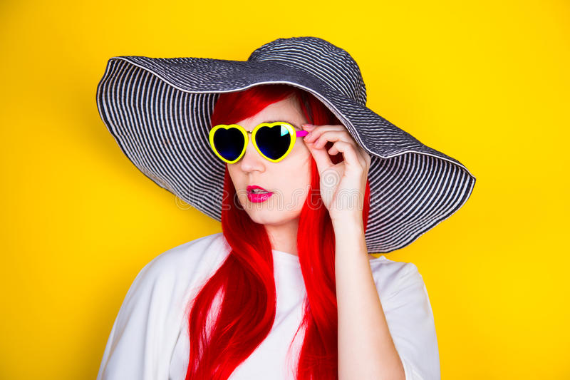 Attractive red-haired young woman in sunglasses and hat on yellow background stock images