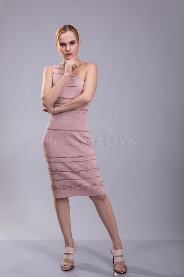 Attractive red head woman posing in light dress on grey background royalty free stock images