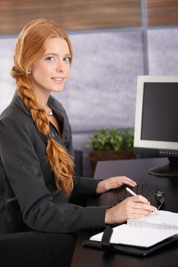 Attractive redhead businesswoman at work royalty free stock photography