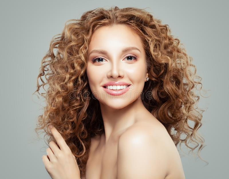 Attractive redhead girl with clear skin and long healthy curly hair. Beautiful female face on gray background royalty free stock images