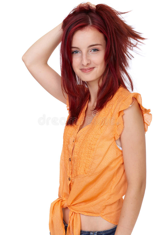 Attractive redhead girl in orange shirt, isolated stock image