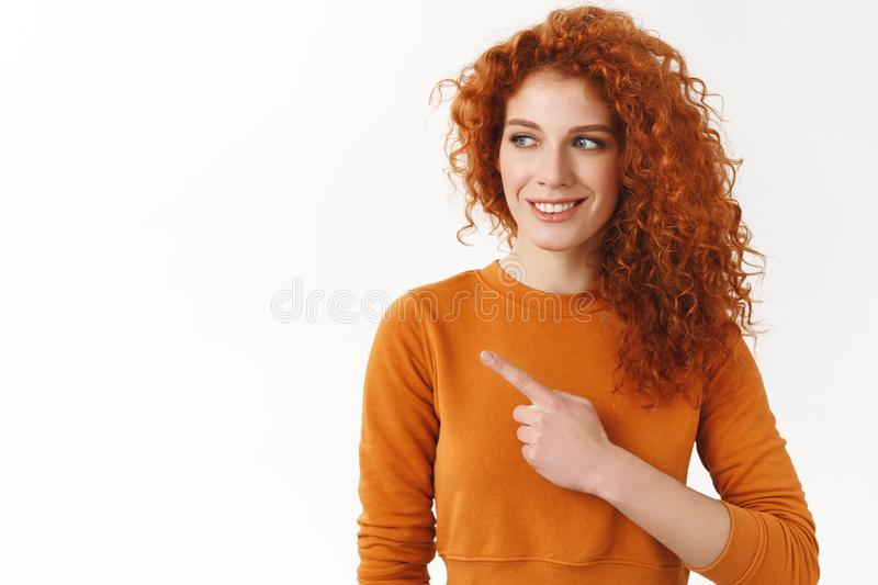 Attractive redhead woman with curly hair curiously peeking and pointing left, checking out interesting copy space promo royalty free stock images