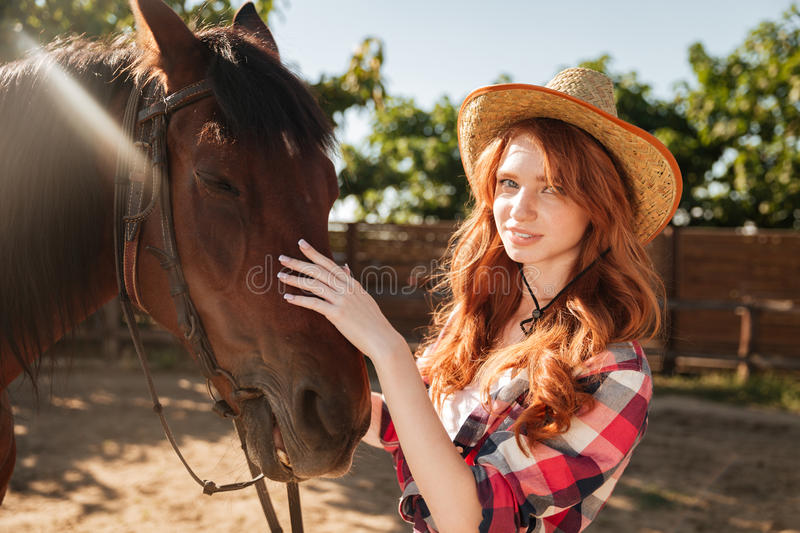 Attractive redhead young woman cowgirl in hat with her horse royalty free stock photo