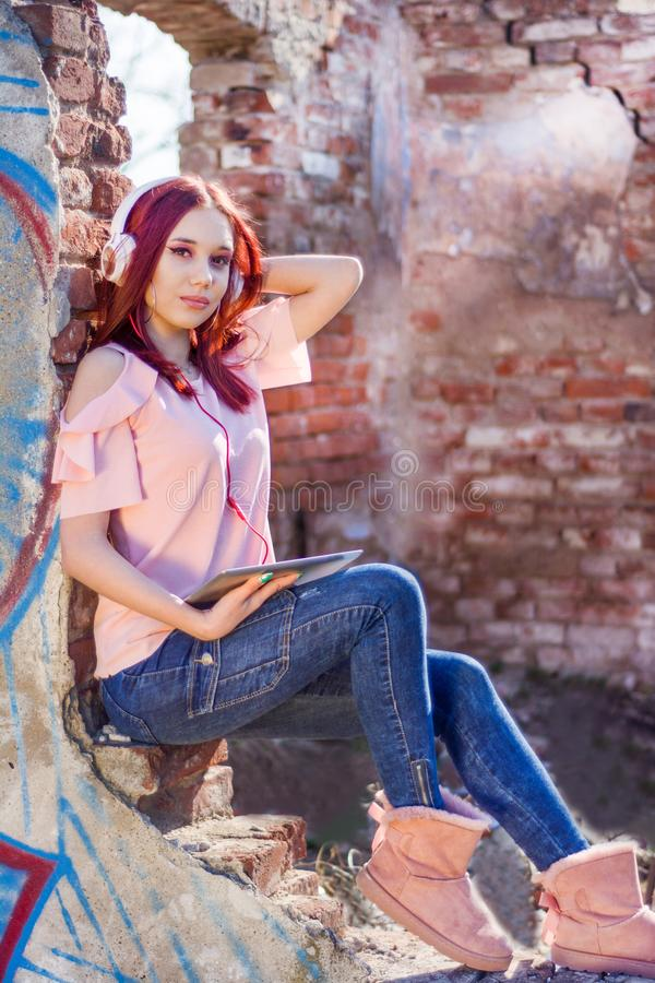 Attractive redheads girl with digital tablet listening to music on headphones on ruins wall red bricks of house in sunset stock images