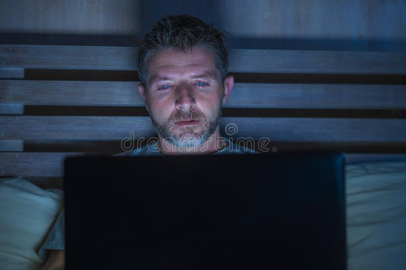 Attractive and relaxed internet addict man networking concentrated late at night on bed with laptop computer in social media. Young aroused man alone in bed royalty free stock photo