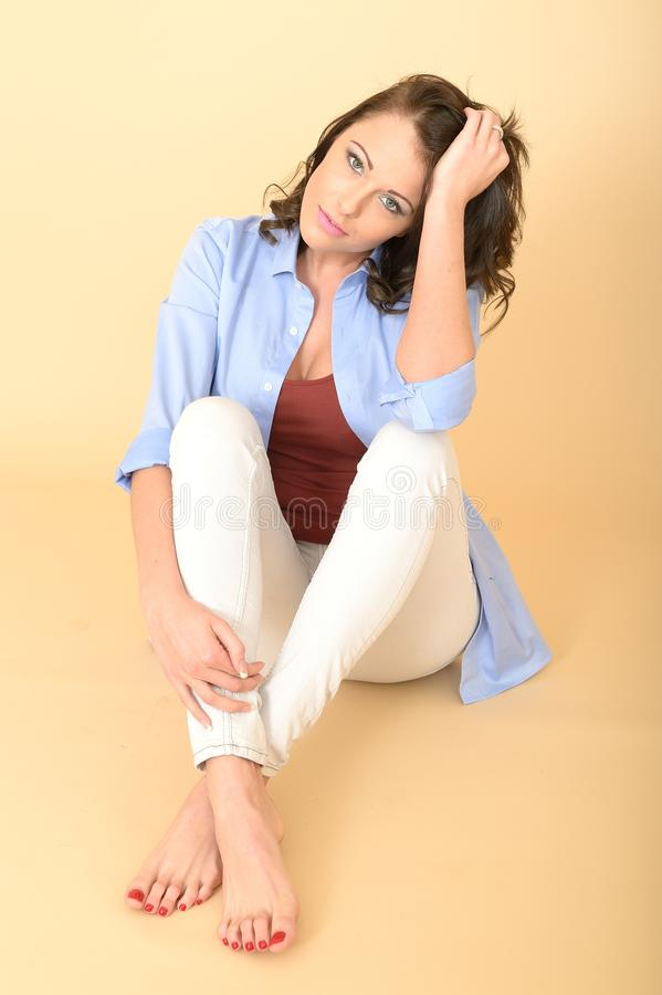 Attractive Relaxed Young Woman Sitting on the Floor royalty free stock photo