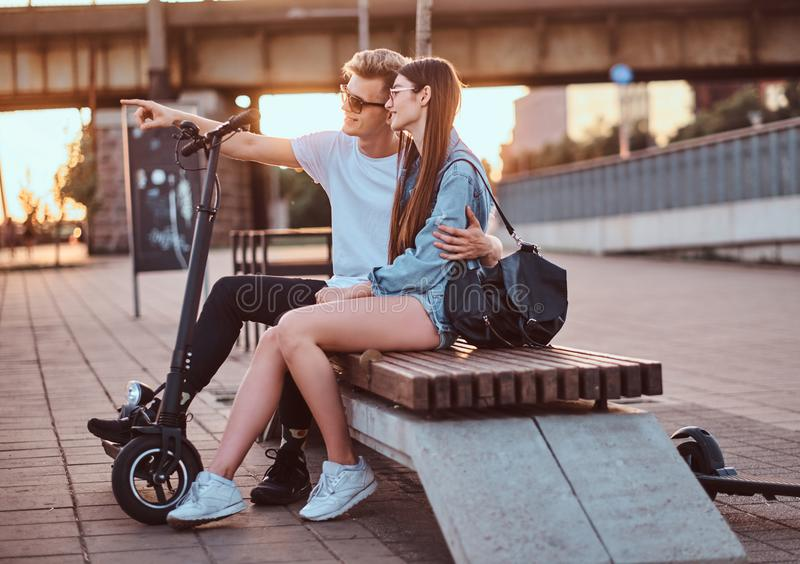Beautiful couple are enjoying sunset on the bench. Attractive romantic couple is enjoying sunset with their scooters while sitting on the bench, guy showing royalty free stock photo