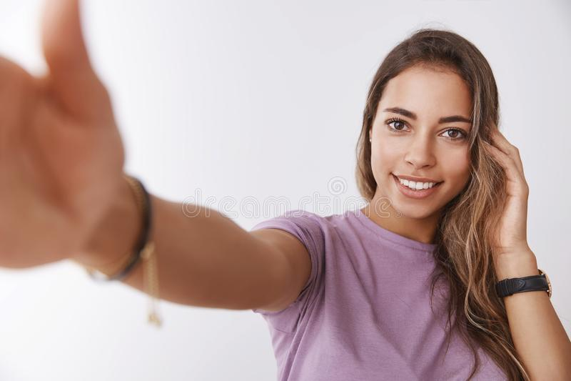 Attractive romantic flirty young 25s woman playing hairstyle messy hair extend hand holding camera like smartphone royalty free stock photography