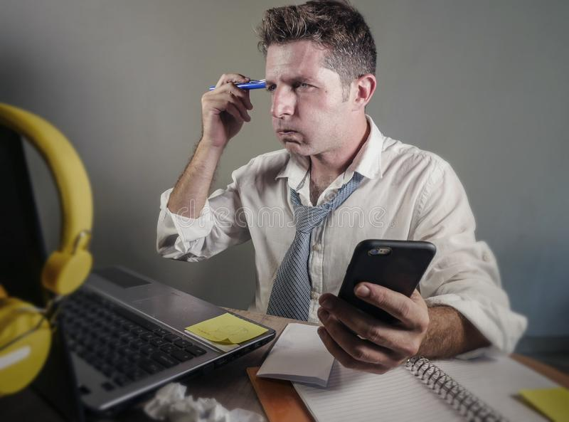 Attractive sad and desperate man in lose necktie looking messy and busy working at laptop computer desk in business office problem royalty free stock photography