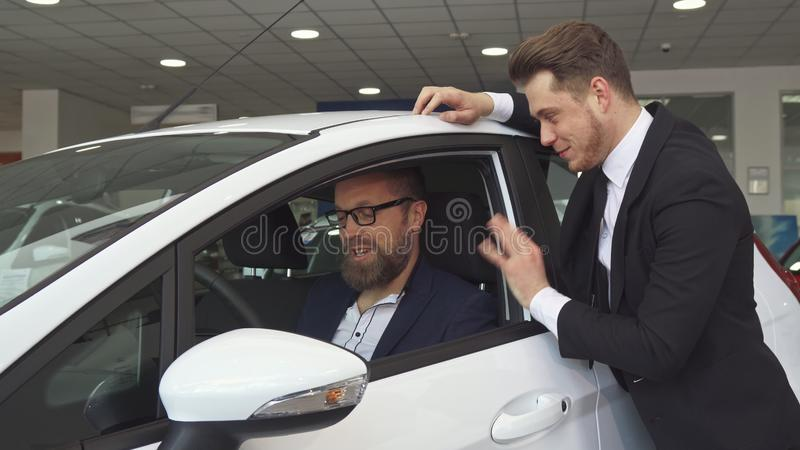 Sales manager consults the customer about the car royalty free stock images