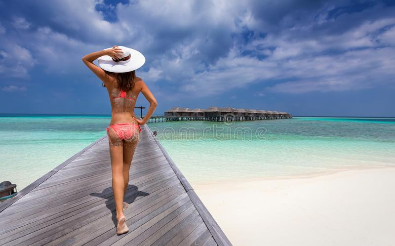 Woman walking over a jetty in the maldives royalty free stock photos