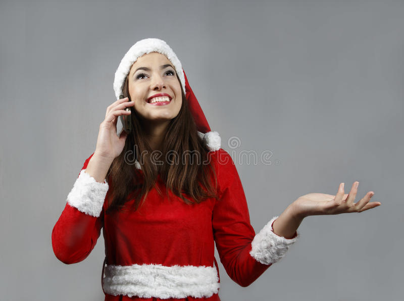 Attractive santa claus girl smiling and make call royalty free stock photography