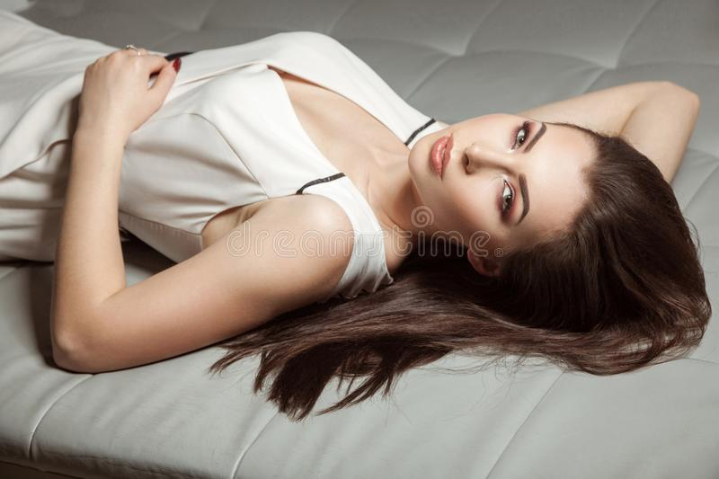 attractive seductive woman in white stylish classic overalls lying on leather sofa royalty free stock image