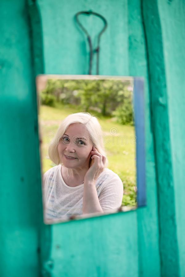 Attractive senior blonde woman looking at herself in mirror stock photos