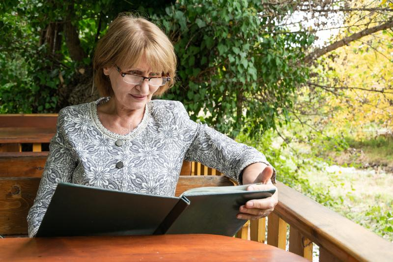 Attractive senior looking a menu in the outdoor restaurant. Healthy  and active lifestyle. Concept stock photography