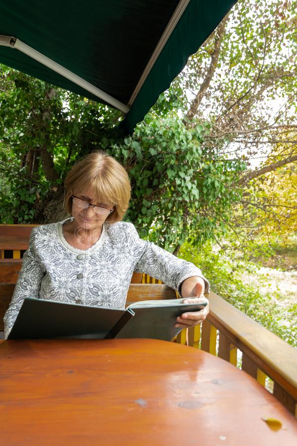 Attractive senior looking a menu in the outdoor restaurant. Healthy  and active lifestyle. Concept stock images