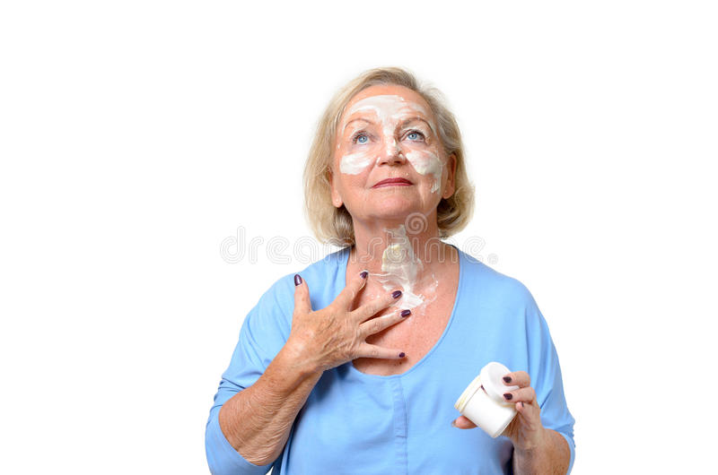 Attractive senior woman applying cream to her skin stock images