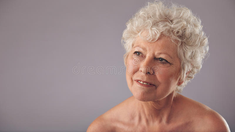 Attractive senior woman daydreaming royalty free stock photography