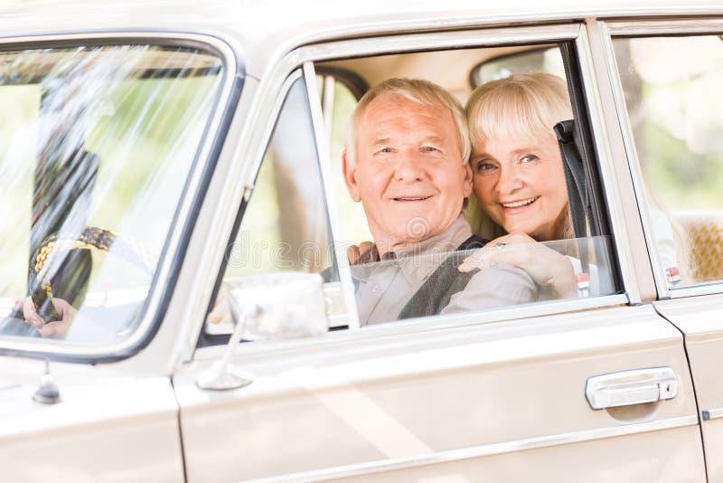 Attractive senior woman hugging man. In vintage car stock photography