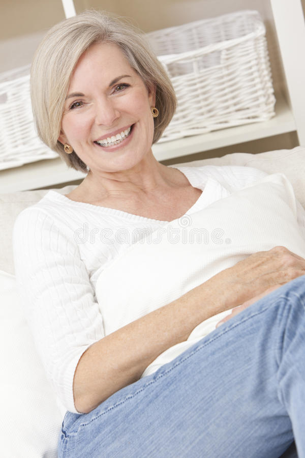 Attractive Senior Woman Relaxing At Home. Portrait of an attractive elegant senior woman relaxing at home on a sofa stock images