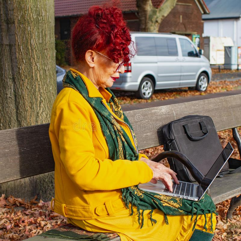 Attractive senior woman retired, female working on laptop , freelance, age and modern technology concept, outdoor workplace stock photo