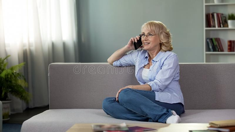 Attractive senior woman sitting on couch and calling daughter, communication stock image