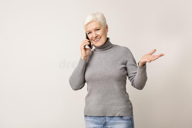 Attractive senior woman talking on mobile phone stock images