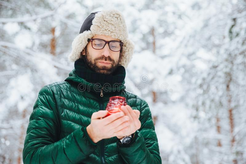 Attractive serious male wears warm winter clothes, keeps candle, stands against winter forest background, enjoys fresh air, being. Very confident. Fashionable royalty free stock image