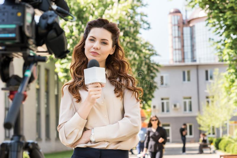 Attractive serious news reporter with microphone looking at digital. Video camera stock photo