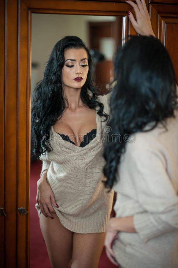 Attractive brunette half naked posing provocatively . Portrait of sensual woman in classic boudoir scene. Long hair woman. Attractive brunette half naked posing royalty free stock photo