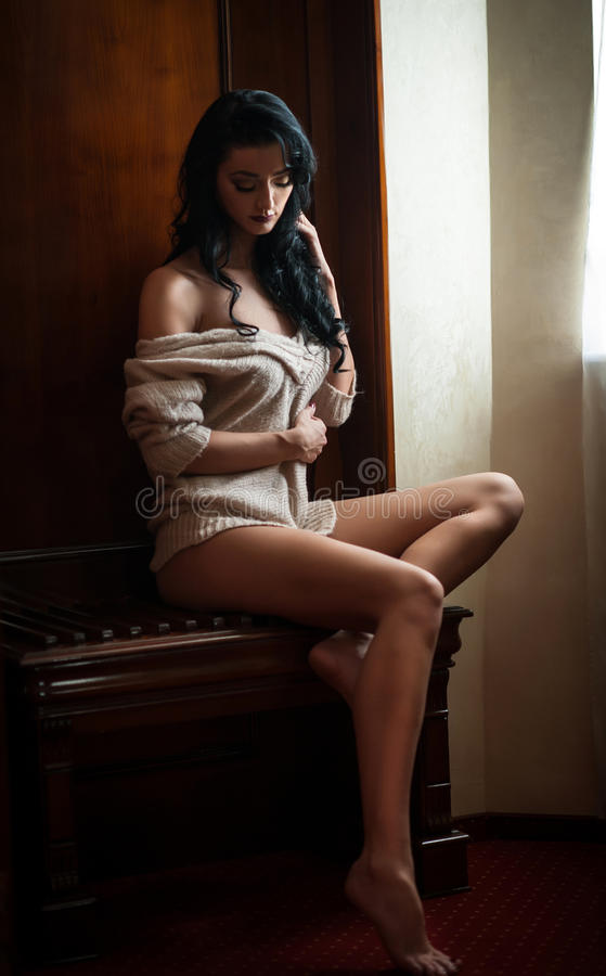 Attractive brunette half naked posing provocatively in window frame. Portrait of sensual woman in classic boudoir scene. Woman with long hair daydreaming and royalty free stock photo