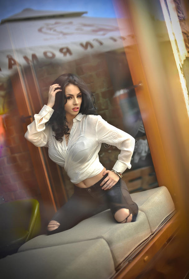 Attractive brunette in white tight fit shirt and black ripped jeans posing provocatively in window frame. Sensual woman royalty free stock image