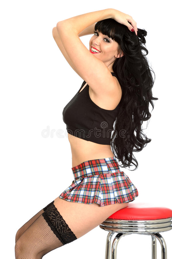 Attractive Flirtatious Young Classic Pin Up Model In Fishnet Stockings and Tartan Mini Skirt. Attractive flirtatious Young classic Pin Up Model or woman with royalty free stock image