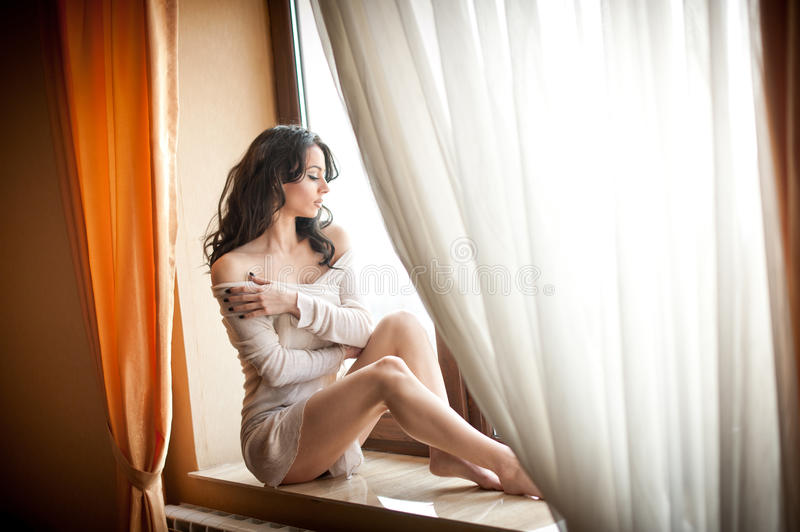 Attractive girl in white dress posing provocatively in window frame. Portrait of sensual woman in classic boudoir scene royalty free stock photography