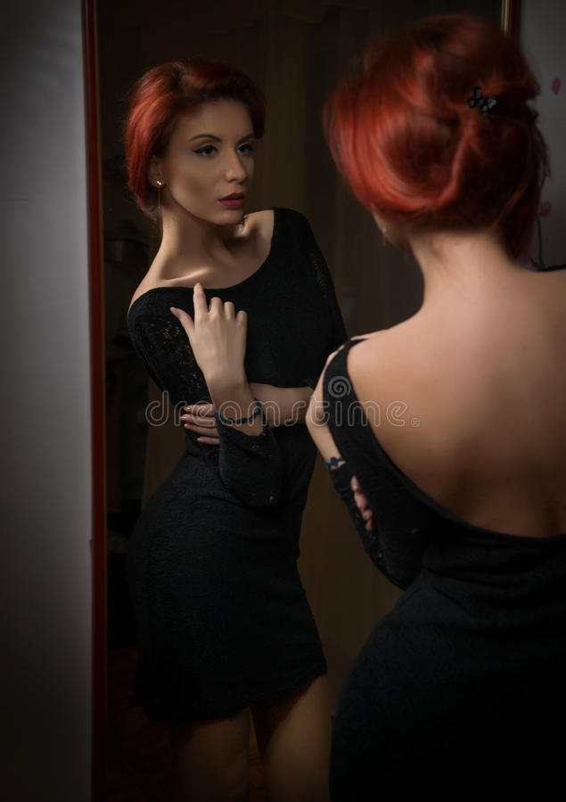 Attractive redhead with black dress posing in front of large wall mirror. Portrait of sensual young woman with red hair. Exposing her back. Beautiful girl with stock image