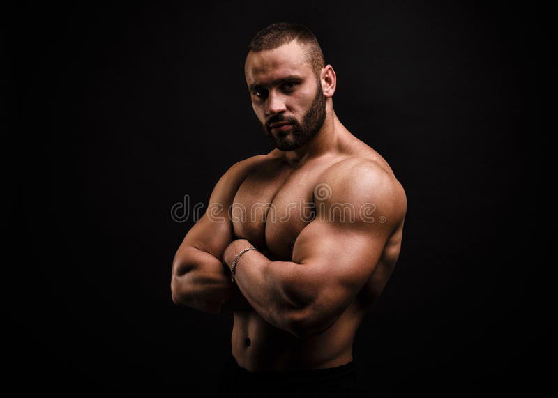 Serious and shirtless bodybuilder crossing hands on a muscular chest on a black background. Building muscles concept. royalty free stock photography