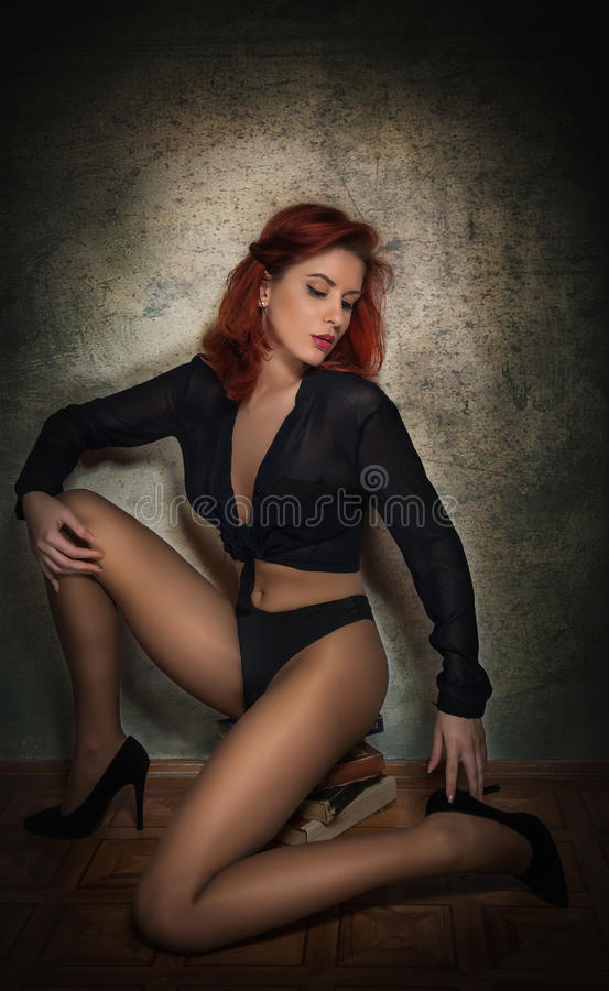 Attractive young woman in black shirt and panties sitting on a pile of books on the floor. Sensual redhead with long legs stock images