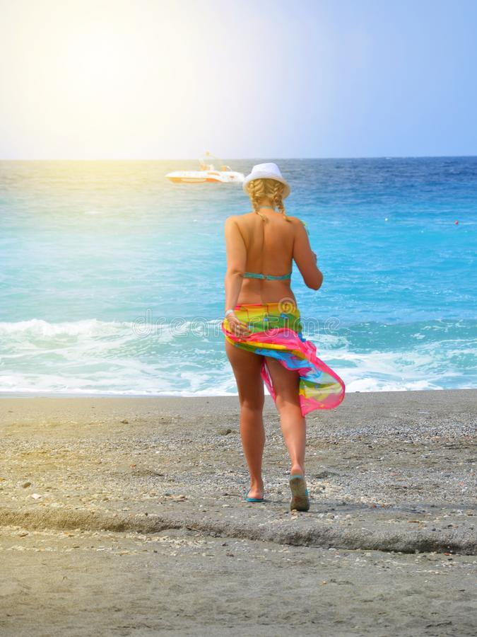 Attractive sexy young woman walks on the beach in a bikini and colorful pareo, luxurious summer vacation, vertical shot, sun rays. And glare walking hat back stock photos