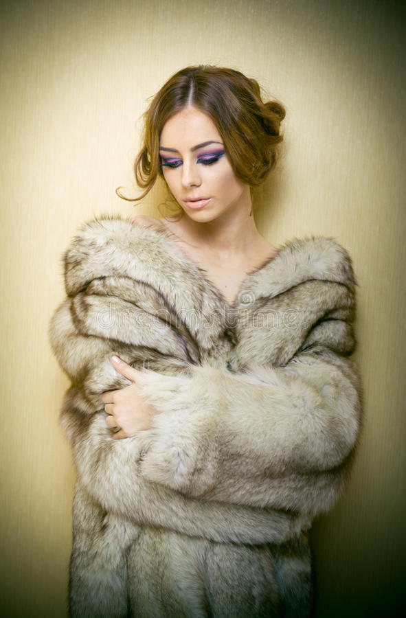 Attractive young woman wearing a fur coat posing provocatively indoor. Portrait of sensual female with creative haircut. Studio shot. Beautiful girl covered royalty free stock photo