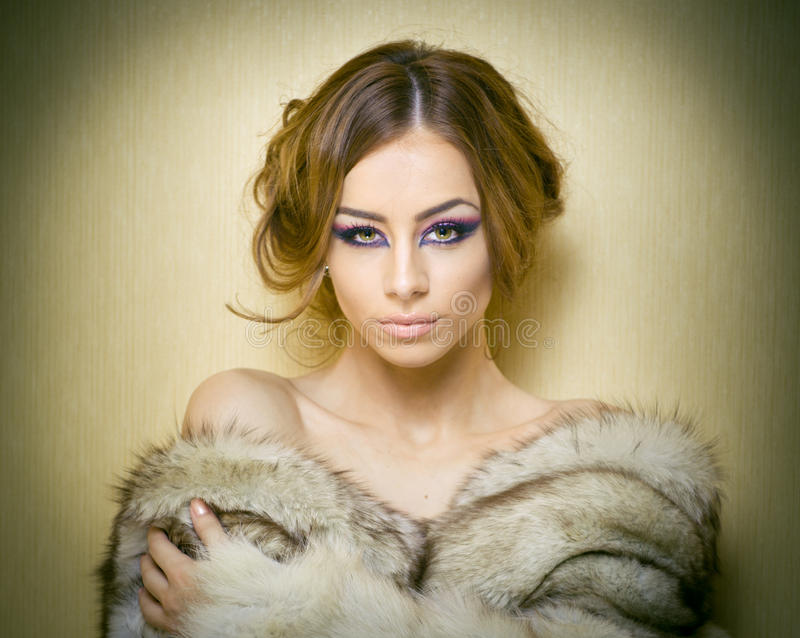Attractive young woman wearing a fur coat posing provocatively indoor. Portrait of sensual female with creative haircut. Studio shot. Beautiful girl covered royalty free stock image