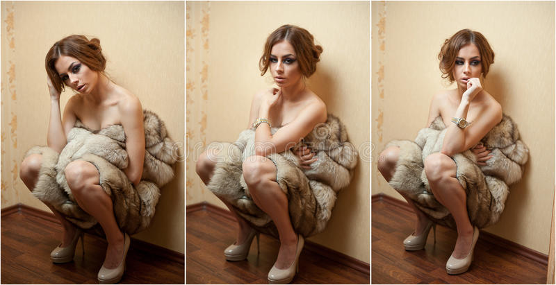 Attractive young woman wrapped in a fur coat sitting on the floor in hotel room. Sensual redhead female being sad royalty free stock photography