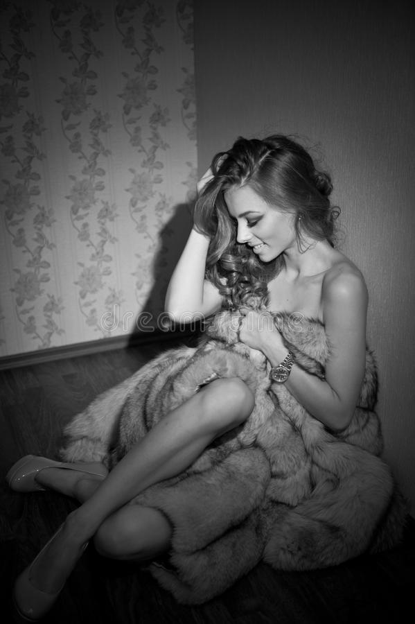 Attractive young woman wrapped in a fur coat sitting in hotel room. Black and white portrait of sensual female daydreaming royalty free stock photos