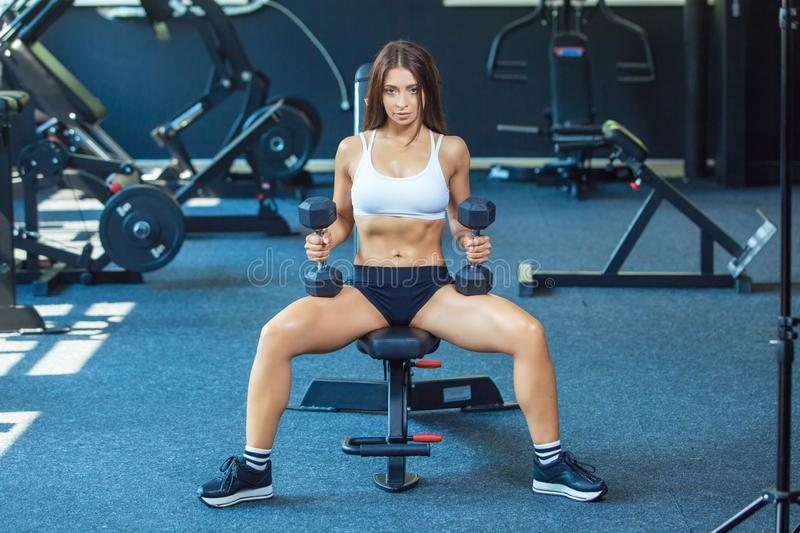 Attractive shape young sporty focused fitness girl doing biceps exercises while sitting on the training apparatus and royalty free stock photography